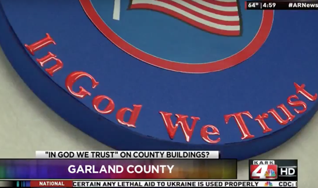 """In God We Trust"" on a blue sign"